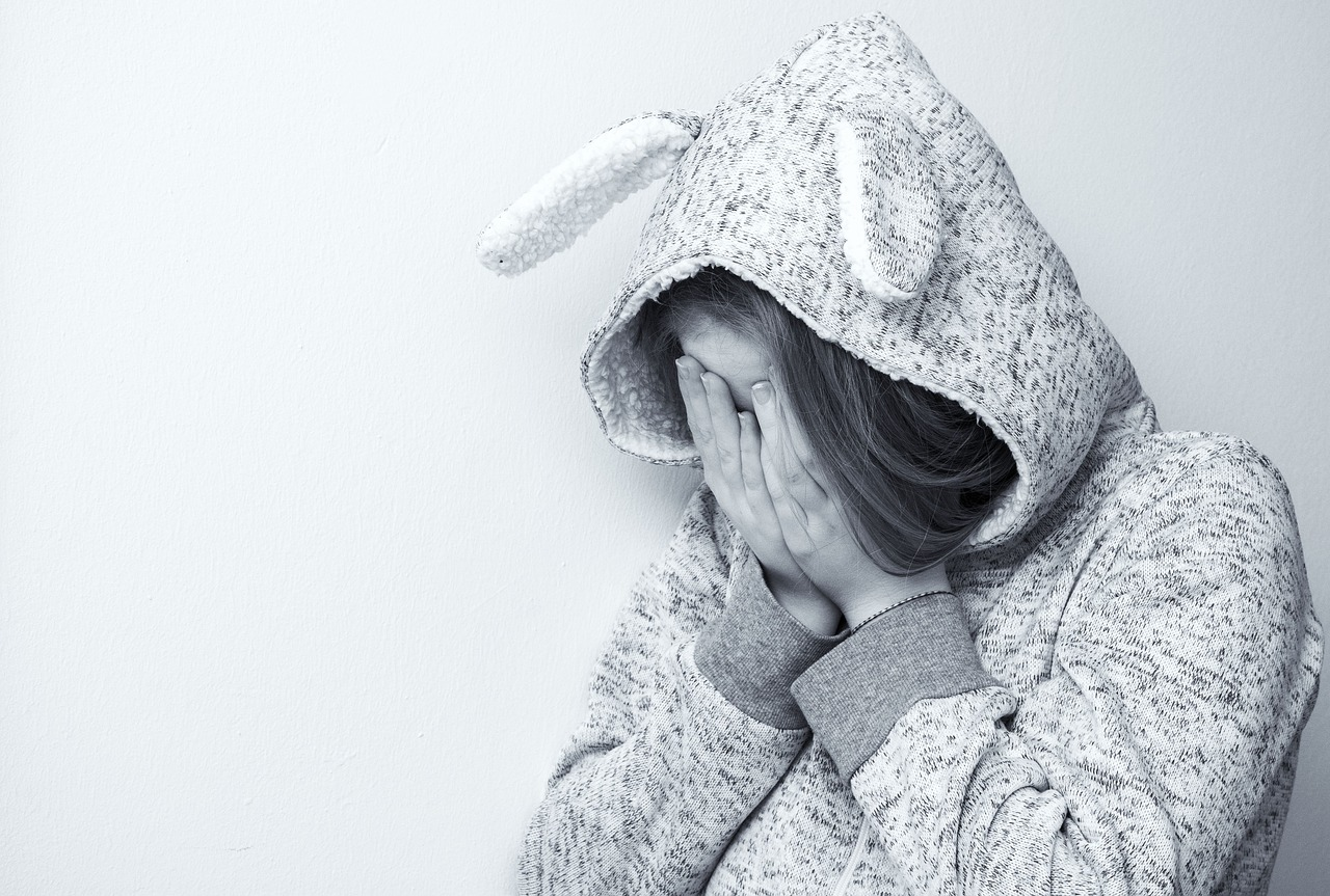 a depressed-looking woman with her face hidden by her gray hood
